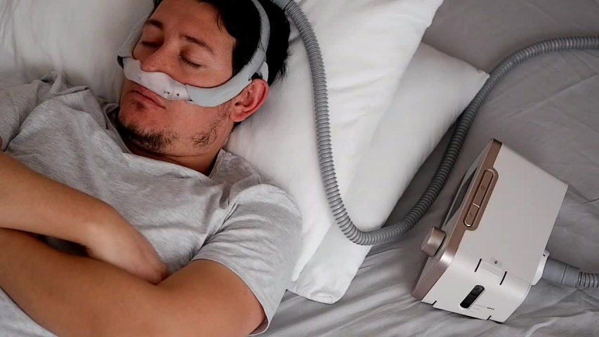 Close-up of healthy young adult man wearing under the nose nasal mask ( CPAP mask ) and using CPAP machine for sleeping smooth without snoring. Royalty-Free Stock Footage #1044469777