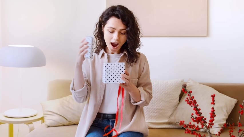 A young happy woman catches and opens a gift box. A female receives a gift, opens and smiles. Holiday and surprise concept.