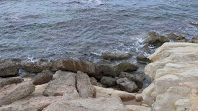 Close-up view of the rocks with small ocean water splashes along the coastline seashore in Paphos, Cyrpus.