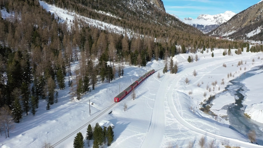 Bernina  Express, red train of Bernina near Pontresina. Aerial view over the forest in winter season. Unesco World Heritage in Swiss Alps.