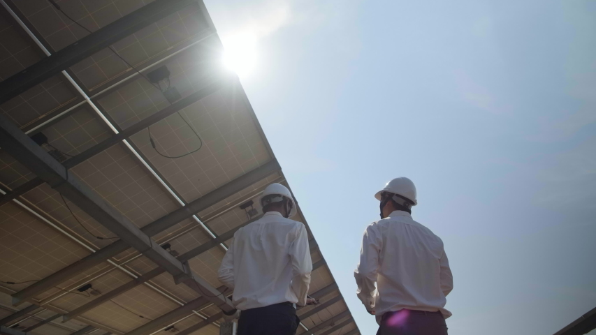 Technician and investor walking in Solar cell Farm through field of solar panels checking the panels at solar energy installation.Solar cells will be an important renewable energy of the future.