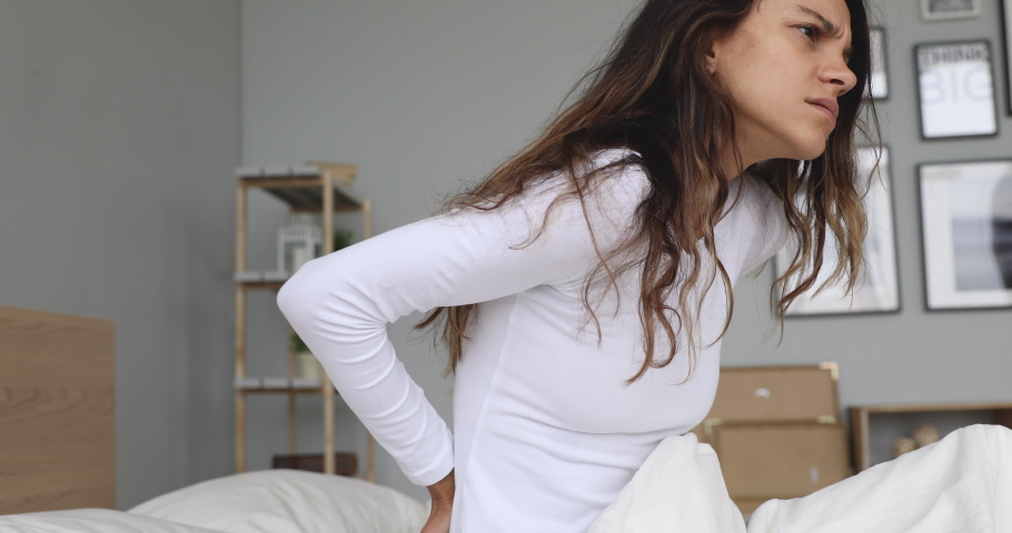 Stressed mixed race woman waking up in morning, sitting on bed, rubbing lower back. Unhappy young lady feeling strong ache, suffering from fibromyalgia after sleeping on uncomfortable mattress.