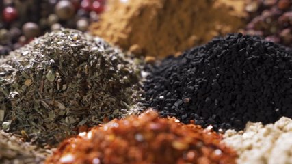 Spices. Various Indian Spices on wooden table. Assortment of Seasonings, condiments. Cooking ingredients, flavor. Slow motion video