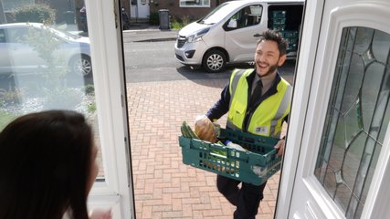 Online Grocery shopping delivery - The driver from Supermarket delivers crate of food to customer at home  -4K Stock Video clip footage