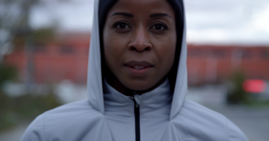 Close up portrait of jogger putting on hood and looking determined into camera, medium close | Shutterstock HD Video #1044535783