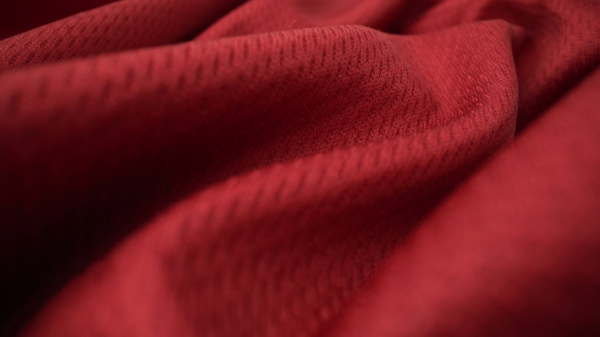 Close up detailed cloth texture of shiny spandex lycra cloth flowing with dolly shot in macro close-up view. Wavy clean elastic weave material. Textile abstract background. Clothing industry concept.