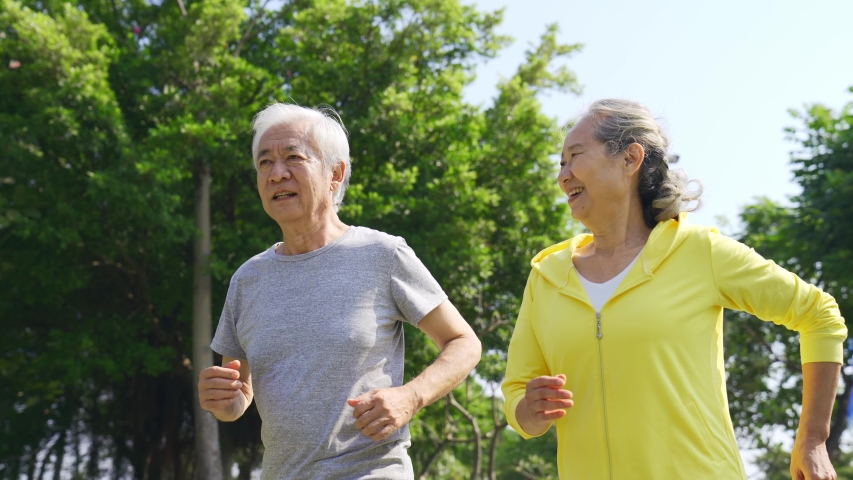Happy senior asian couple exercising running outdoors