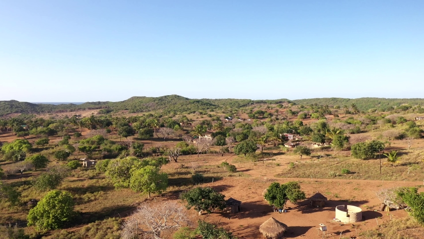 Aerial Tilt-Down Cinematic Shot of Chidenguele Village Showcasing Traditional African Huts and Plantations Royalty-Free Stock Footage #1044552850