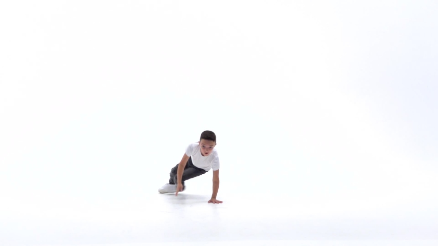 Little boy is dancing a modern dance on the white background in black leather jackets and jeans. Slow motion. | Shutterstock HD Video #1044564502