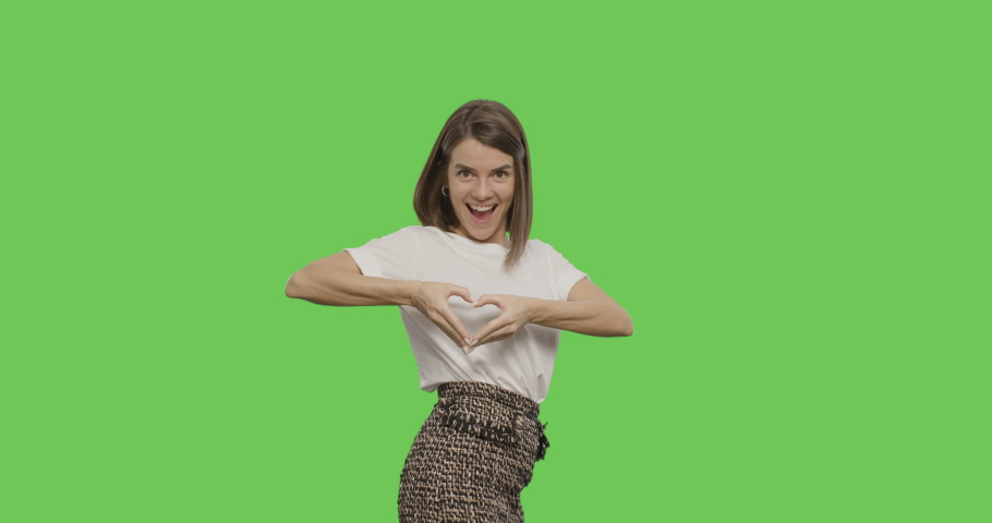 Close-up of smiling young woman making sign heart shape by hand posing at green screen studio background. background, Chroma Key 4k video footage slow motion 60 fps | Shutterstock HD Video #1044589471