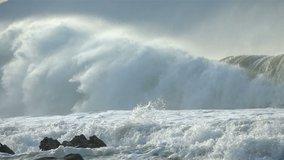 Extreme Ocean Wave crushing coast. Power of waves breaking splashing sea-spray water foam
