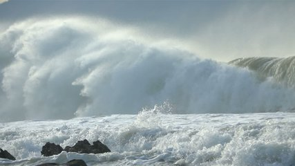 Extreme Ocean Wave crushing coast. Power of waves breaking splashing sea-spray water foam