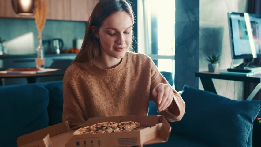 Cheereful european young woman in brown sweater sitting on sofa at modern living room and greedily eating tasty pizza, enjoying and smiling. Fast food addiction. Slow motion. Royalty-Free Stock Footage #1044602302