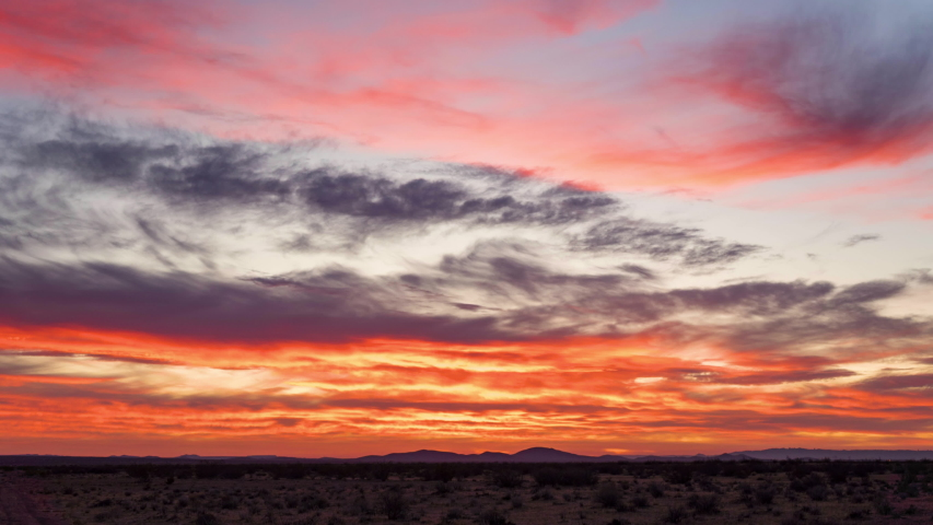 Fiery red and orange sunrise timelapse in cloudy Mojave Desert