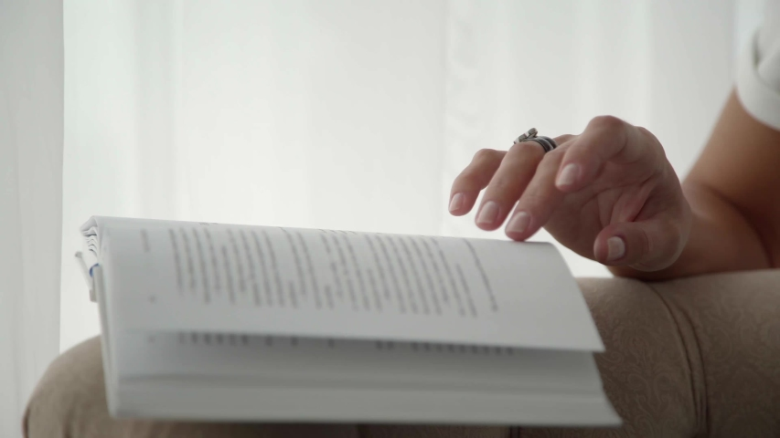 An open book in front of a woman, only her hands in the frame, mug with coffee nearby. Process of reading, turning pages. Book is sideways against a background of light textile (curtains), in interior | Shutterstock HD Video #1044639532