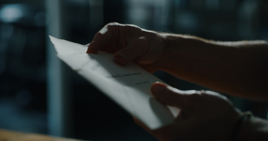 Cinematic close up shot of man is putting a letter in an envelope before sending it. Concept of correspondence, calligraphy, communication