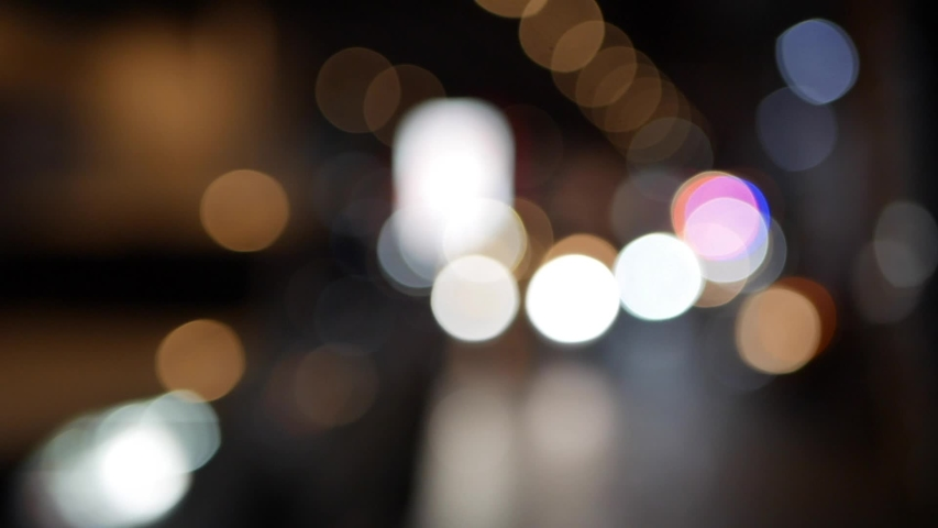 Beautiful glittering bokeh in dark blurry background at night. The round colorful bokeh shine from car lights in traffic jam on city street. Out of focus with blurry. Unfocused city lights. Traffic | Shutterstock HD Video #1044659404
