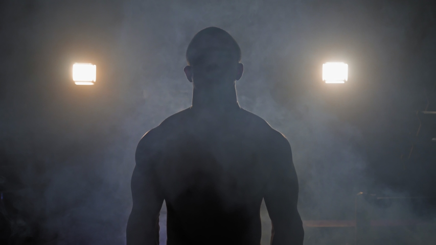 Muscular man doing crossfit training in a dark shadowy gym lifting weights holding a barbell at waist level in a health and fitness concept, movement round shot