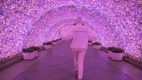 woman in a white sweater and hat walks through a pink glowing tunnel at night in Moscow in the new year 2020