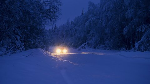 The car drives on a snowy forest road through snowfall in the evening. Snowflakes are highlighted and glare. Dark blue winter landscape during snowstorm.
