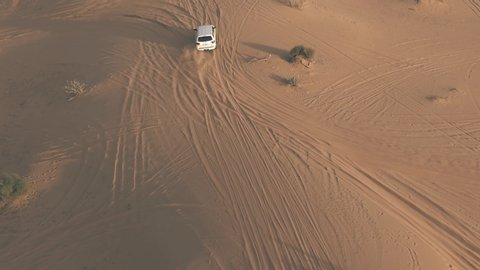 Aerial tracking shot of an unknown white SUV driving fast along sand dunes in the desert