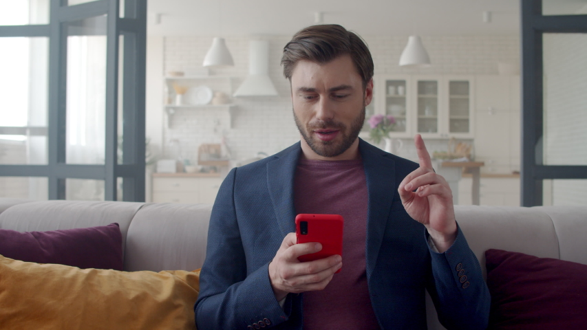 Closeup focused business man reading email on phone at home office. Portrait of male freelancer getting idea at remote workplace. Handsome guy texting on smartphone on couch in slow motion. Royalty-Free Stock Footage #1044682687