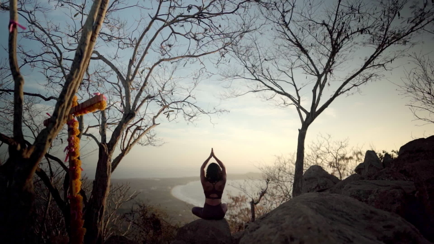 Young woman sits in namaste pose meditating on a beautiful mountain as sun sets in the distance | Shutterstock HD Video #1044687295