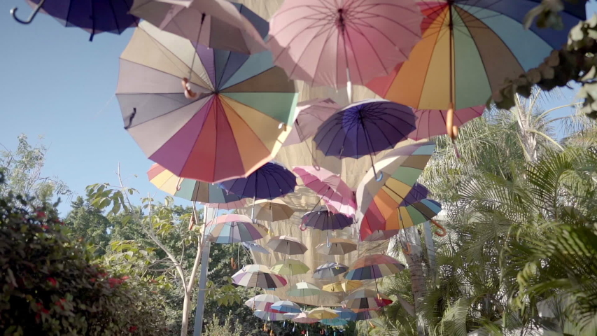 POV walk along street with a floating canopy of colorful umbrellas