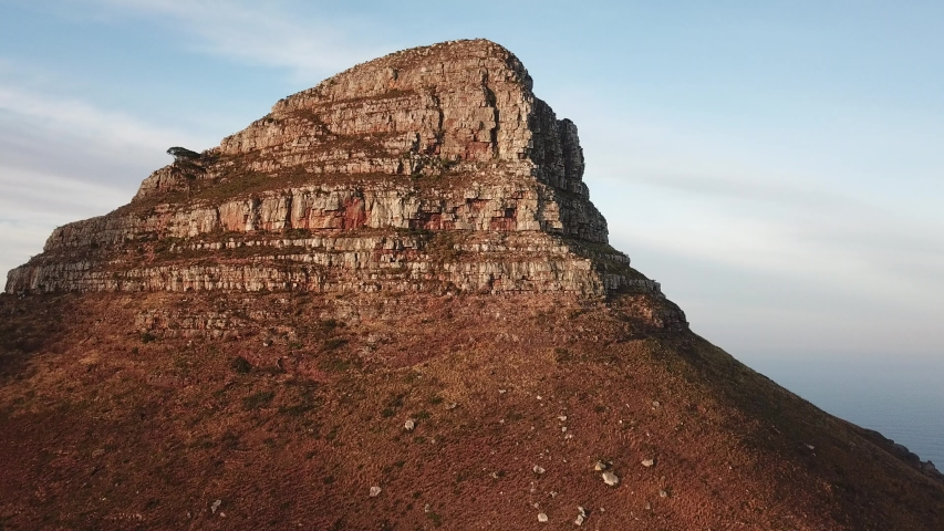 4K high quality aerial sunny morning footage of spectacular scenic Lion's Head Mountain, rocky hills with hiking trails, Atlantic Ocean coast panorama in Western Cape, Cape Town, South Africa