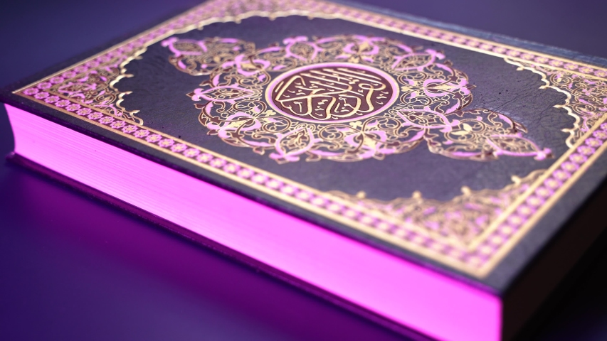 Quran Islam holy book of Muslims with rgb color led light effect , the Quran, is placed on table , Holy Quran with arabic calligraphy meaning of Al Quran, islamic background  | Shutterstock HD Video #1044708100