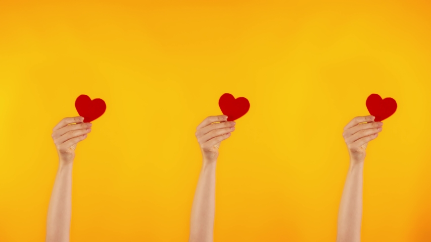 Demonstration of love. Three female hands are holding red hearts. A blogger gets likes on social networks.