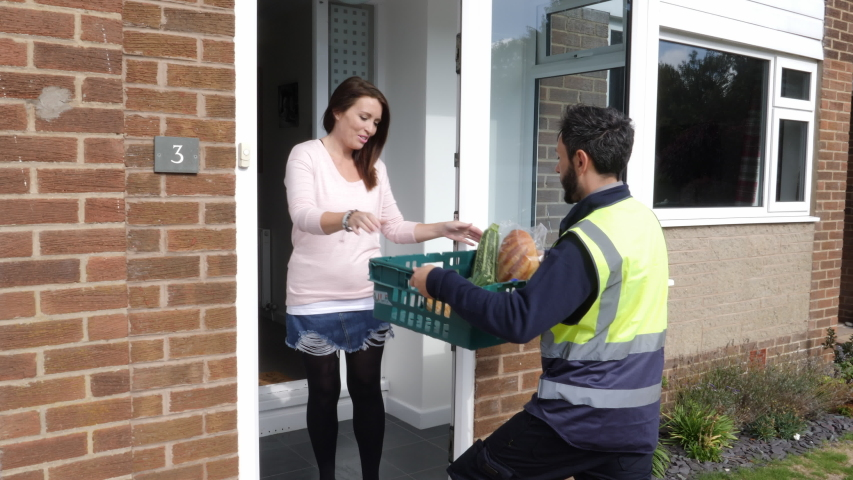 Online Grocery shopping delivery - The driver from Supermarket delivers crate of food to customer at home outside  -4K Stock Video clip footage | Shutterstock HD Video #1044711841