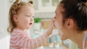 Handheld view of mum and little girl playing with flour. Shot with RED helium camera in 8K