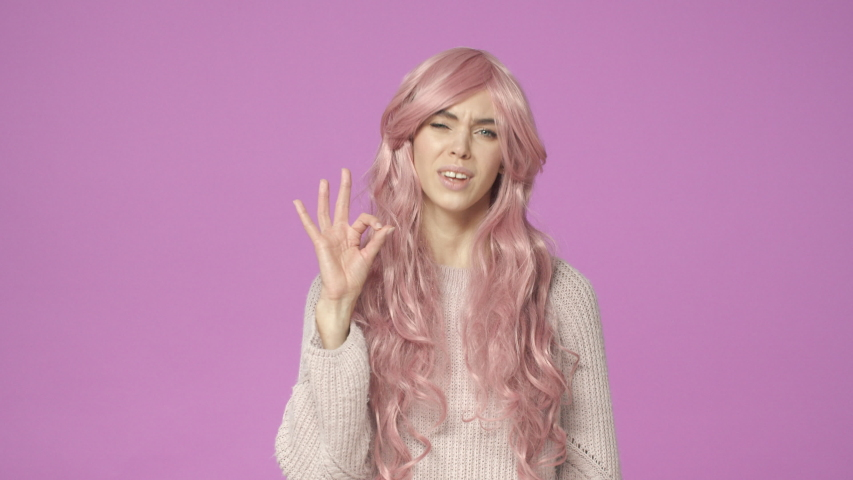 It was good. Slow-motion cute, adorable european woman in pink wig, agree with friend, showing alright, okay gesture, assure all ok, everything fine, agree or approve something, purple background