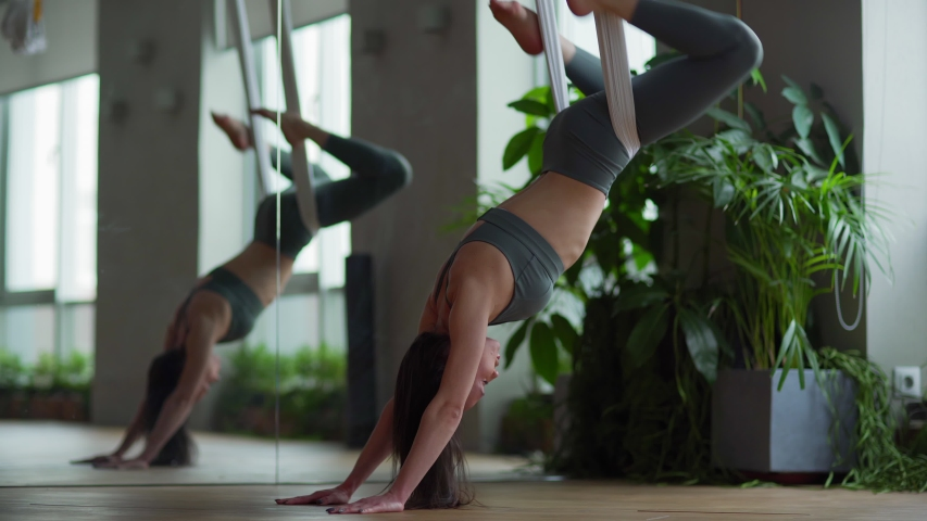 Medium shot of fit young woman doing aerial yoga exercise stretching her back and swinging legs while hanging upside down on hammock in antigravity yoga studio Royalty-Free Stock Footage #1044725242