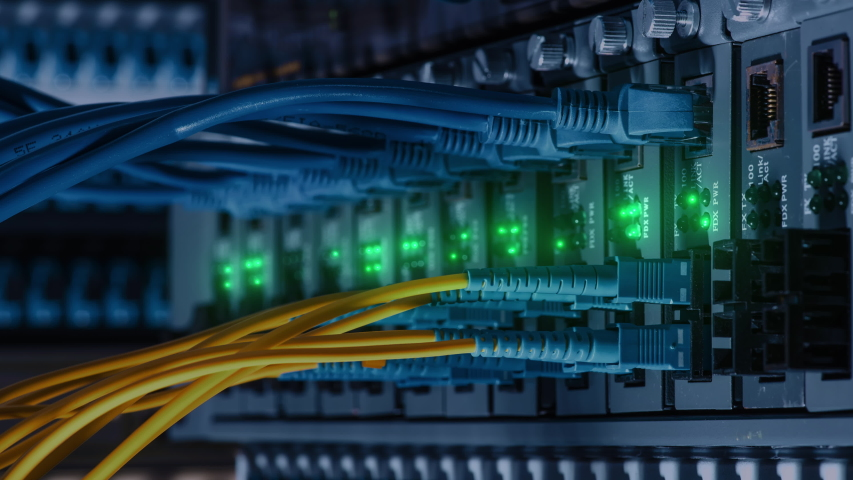 Close up fiber optic in server room. Network cables installed in the rack at data center. Ethernet cable on network switches background | Shutterstock HD Video #1044736879