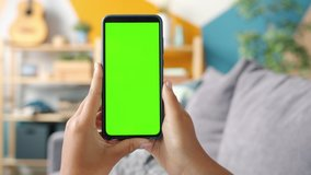Close-up shot of green screen template smartphone in female hands at home, girl is watcing content without touching gadget screen. Modent technology and information concept.