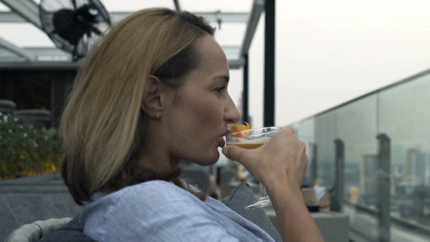 Young, happy woman relaxing and drinking cocktail in skybar | Shutterstock HD Video #1044765106