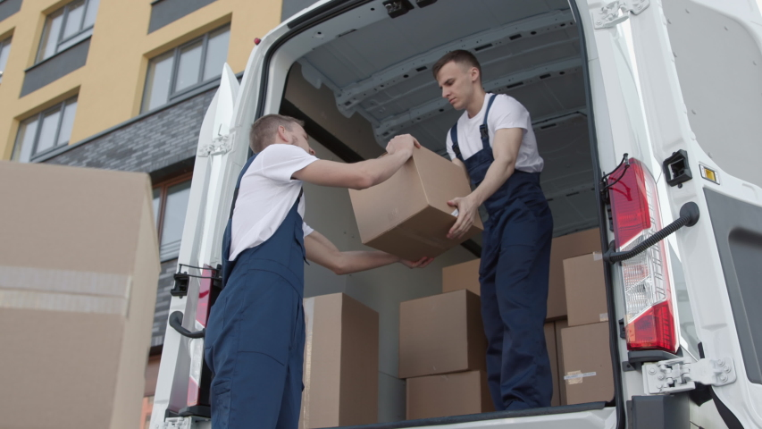 Professional Workers on Stacking Boxes for Transportation. Concept of Trade Transit on Truck or Carriage on Van. Lifestyle of Friendly Delivery Man at Job of Putting Carton Packs in Lorry for Convey Royalty-Free Stock Footage #1044773476