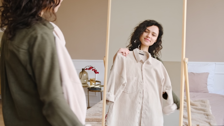 Young woman getting dressed looking in mirror. Trying on clothes enjoying herself.  Royalty-Free Stock Footage #1044776293
