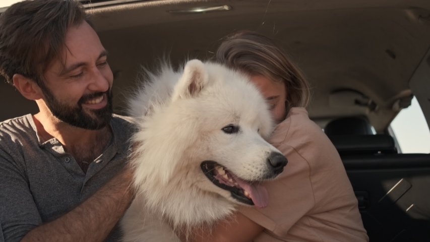 A happy smiling couple man and woman are petting and hugging a dog while sitting in the car trunk | Shutterstock HD Video #1044783817