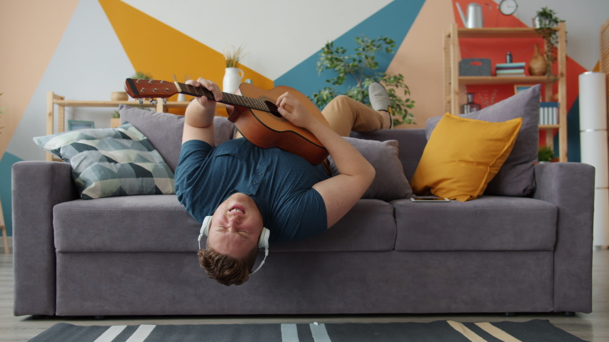 Joyful guy is playing the guitar singing wearing headphones having fun on sofa at home. Modern entertainment, music and happy young people concept. | Shutterstock HD Video #1044790741