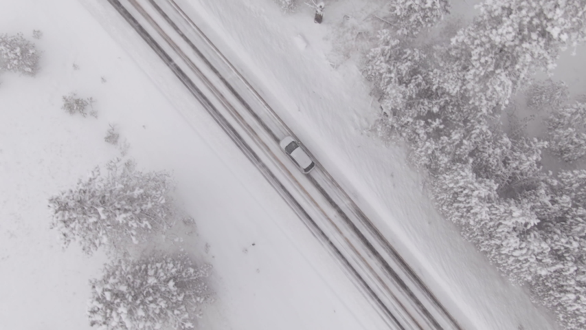 DRONE, TOP DOWN: Car drives through a slippery snow covered intersection in Spokane, Washington. Flying above a car driving down icy road as blizzard covers the landscape with a deep blanket of snow.