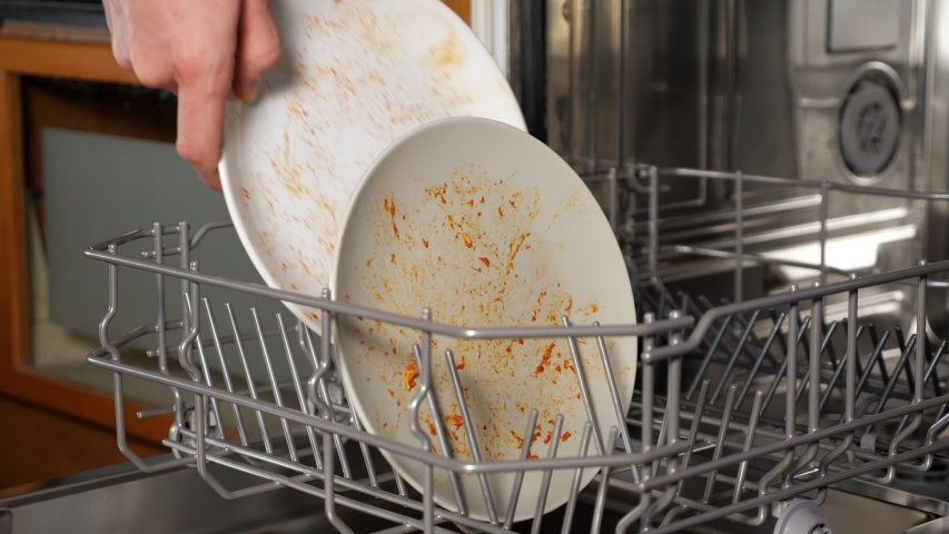 Person puts dirty dishes and cutlery into modern dishwasher after having supper in kitchen extreme close view