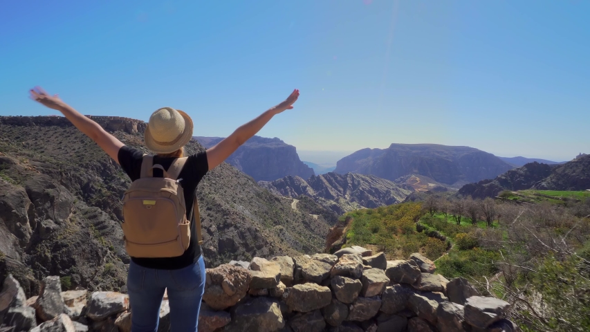 Young Foreign Female Tourist Enjoying the View of Omani Mountains at Jebel Akhdar Gorge in Al Hajar Range, Oman. Woman in Active Solo Travel in Middle East Countries