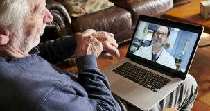 Senior man following the advice of his doctor during a telemedicine appointment while moving his wrist around to evaluate an illness or injury