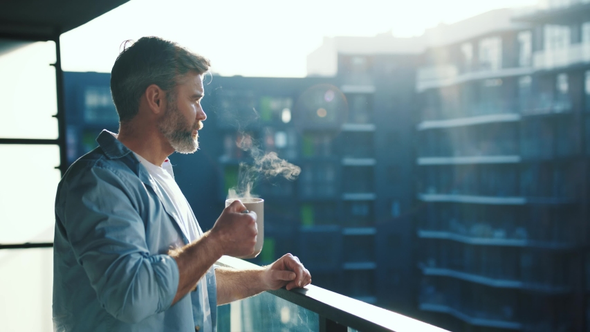 Handsome caucasian middle aged man stands in the balcony with great views and drinks hot coffee or tea, sun shine, enjoying beautiful morning feeling happy