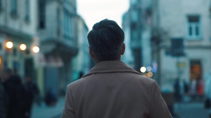 Back view of unrecognizable man walks along the city center street looks around city lights on background business downtown evening happy close up slow motion  Royalty-Free Stock Footage #1044817249