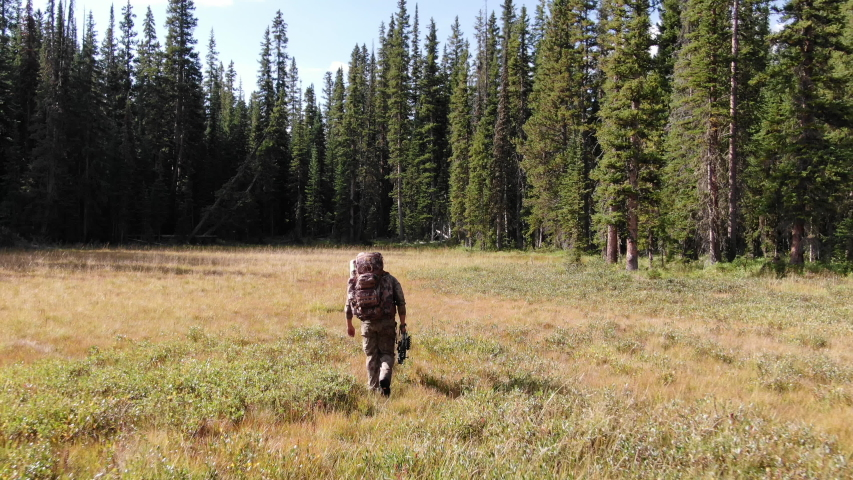 Aerial of Camo Hunter Hiking in Colorado Field   Shutterstock HD Video #1044822364
