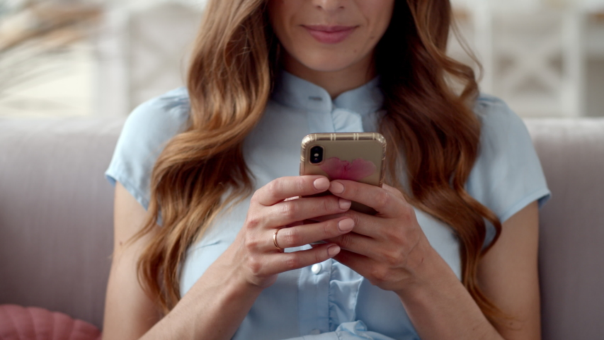 Closeup business woman typing message on mobile phone at home office. Young girl chatting on phone in slow motion. Close up young woman hands using smartphone on couch.